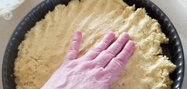 Picture of a hand pressing the dough into the flan pan