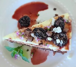 Triple Chocolate Mousse Cake on a plate decorated with cherry sauce