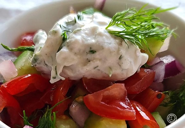 Dairy-Free Tzatziki Sauce on some tomatoes, cucumbers, and red onions