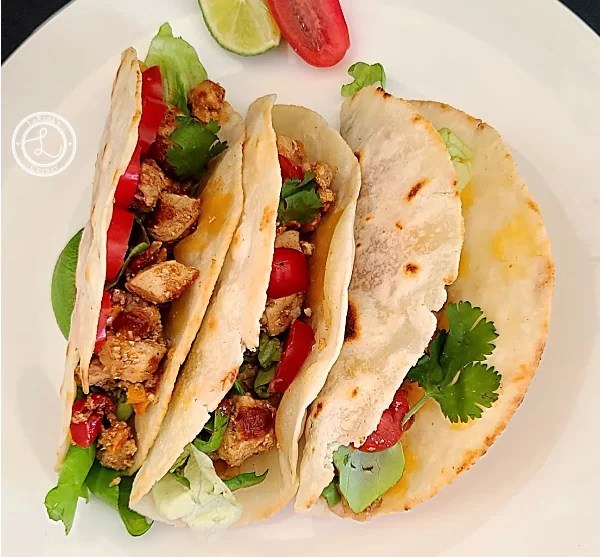 3 Gluten-Free Chicken Tacos on a plate with a wedge of lime and tomato slices.
