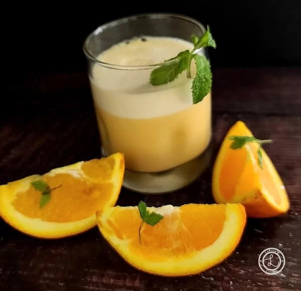 Protein Packed Orange Julius a glass with three slices of orange and sprigs omint.
