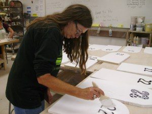 "Darlene Matthews, helps paint the tombstones for the ""22 a Day."" An event that help bring awareness to suicides among military veterans. (Photographer/Anibal Santos)"