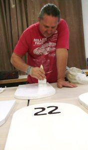 """Ceramics Instructor Steve Dilley prepares a tombstone with the No. 22 on it. 22 tombstones will be prepared for the veteran suicide awareness event, """"22 a Day."""" (Photographer/Anibal Santos)"""