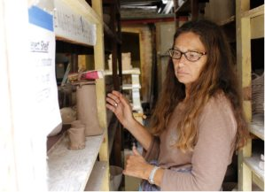 Darlene Matthews looks for her ceramic piece in shelf behind the ceramic kilns. (Photographer/Anibal Santos)