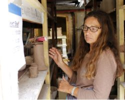 Darlene Matthews looks for her ceramic piece in shelf behind the ceramic kilns. (Photographer/Anibal Santos)
