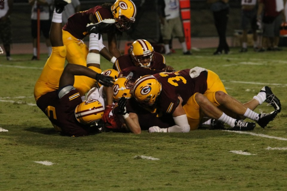 Multiple Gauchos tackle one Palomar player. Saddleback has won two straight games, after losing the first two games of the season. (Nick Nenad/Lariat)