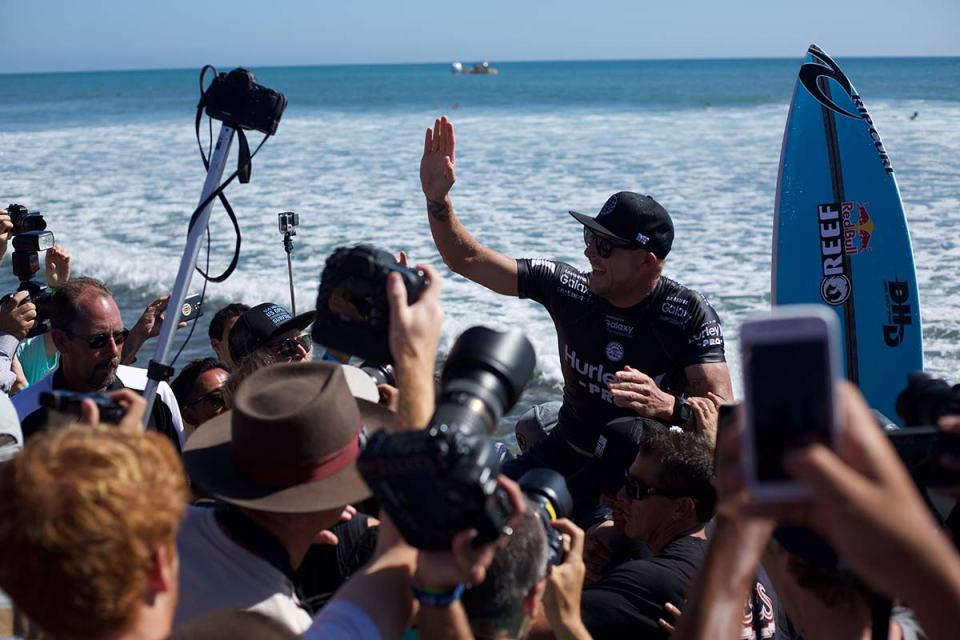 Mick Fanning makes his way up the beach after winning the 2015 Hurley Pro at Trestles. (Niko LaBarbera)