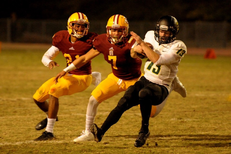 Sophomores Zachary Wade (No. 7, red) and Kai Ross (No. 21, red) attempt to tackle a Golden West College player. The Gauchos finished the season 8-2. (Cliff Robbins)