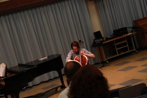 Ryan Fogal plays the cello in front of the audience and master Canadian violinist Iryna Krechkovsky.