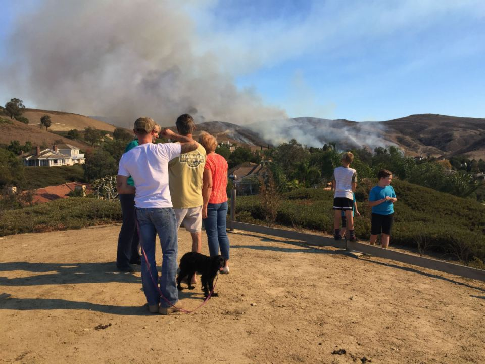 On lookers watch as the fire spread up the hillside. Mackenzie Quinn