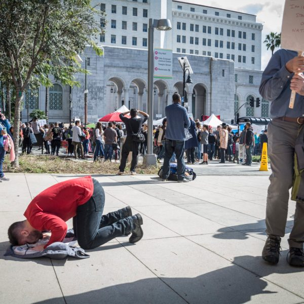 A man praying with a feeling of high emotions amongst fellow protestors. (By Jorge Maldonado)