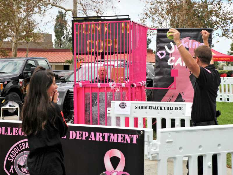 A Saddleback student hits the bullseye, sending Police Operations Lieutenant Michael Betzler into the dunk tank as Police Officer Ryan Maligie cheers her on (Adam Gilles/Lariat)