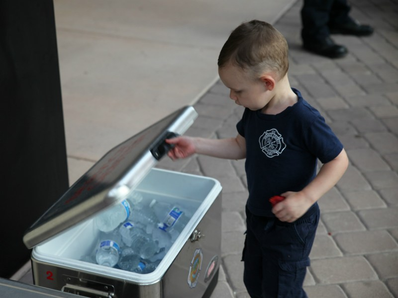 A young boy takes a water break during the homecoming celebration at OCFA (Adam Gilles/Lariat)