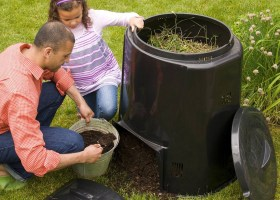 Two individuals looking over a pail full of brown matter to put into their compost bin.
