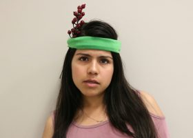 Sandra Reyes poses with her lettuce headband and cranberry flower. Photograph by Lizzie Williams.