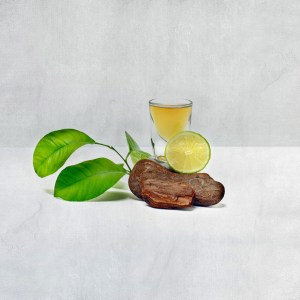 Shot Of Bourbon with a slice of lime and green leaves