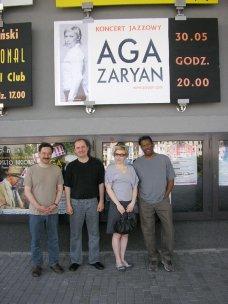 photo of Larry Koonse with Aga Aaryan, Darek Oles, and Munyungo Jackson beneath sign advertising Aga Zaryan show