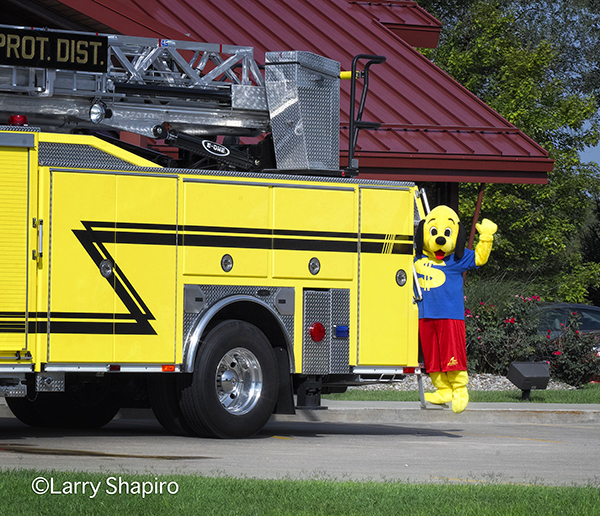 dog mascot posing on a fire truck