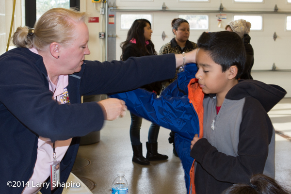 Firemen give winter coats to children