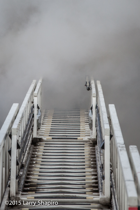 smoke hides firefighters on aerial ladder