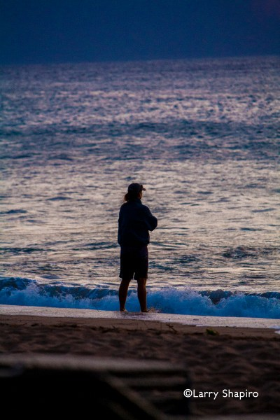 man watching the ocean at dusk