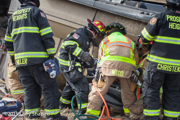 firemen extricate victims trapped in truck