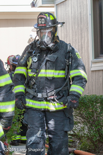 fireman in full PPE exting a house after fighting a fire