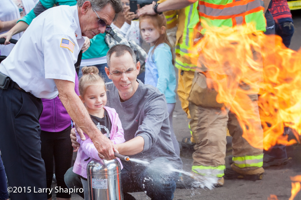 father helps daughter learn to use a fire extinguisher