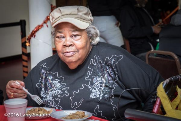African American woman enjoying free Thanksgiving meal
