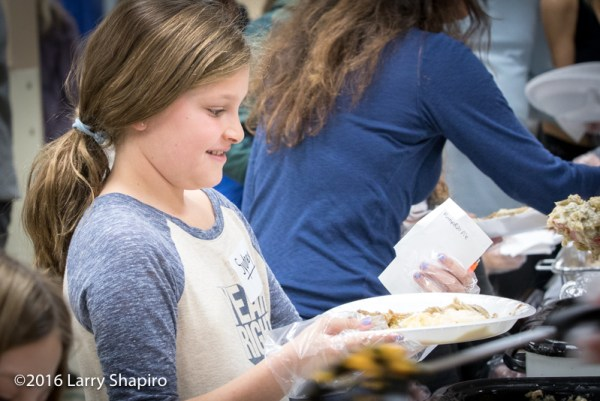 young volunteer serves Thanksgiving dinner