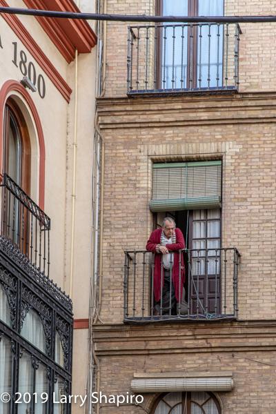 man on balcony in Seville Spain