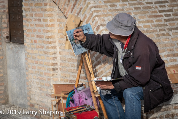 painter painting a landscape in Granada