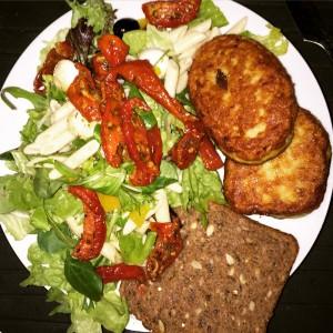 Fiskefrikadeller fra Skagens Fiskerestaurant serveret med en skive fuldkornsrugbrød og salat med oliven, soltørrede tomater og peberfrugt.