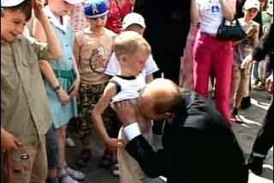 """No, you're not seeing things. That's really the then-""""president"""" of Russia Vladmir Putin lifting a little boy's shirt in broad daylight and kissing his stomach.  Note the reaction of the kid at the left.  Just one of many head-scratching moments from Tsar Putin, and nothing compared to Georgia."""