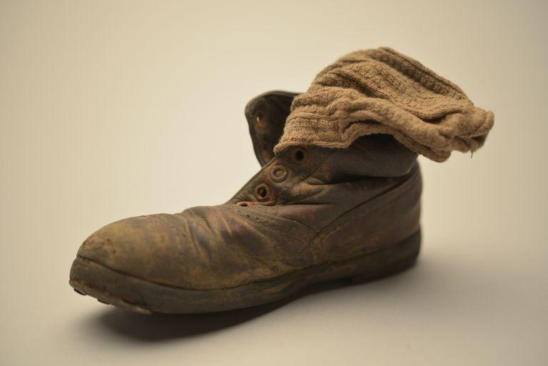 Zapato y calcetín de niño, colección del Museo Estatal de Auschwitz-Birkenau - Foto por Pawel Sawicki © Auschwitz-Birkenau State Museum - Musealia