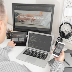 Web designer, programmer working with responsive web template. Multiple devices on desk.