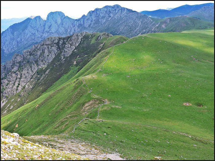 La suavidad del terreno de la veiga Candioches se ve alterada por la verticalidad de la vertiente norteña. Al fondo la peñas de La Mesa