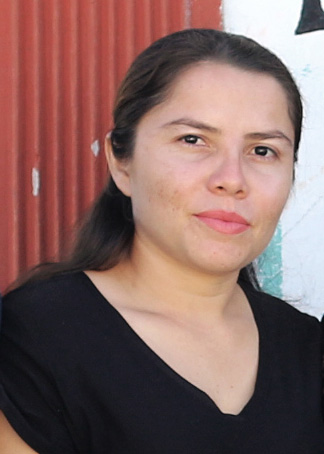 Sharlin Lopez Rodriguez, the LASM Office Assistant stands in front of a wall wearing a black shirt.