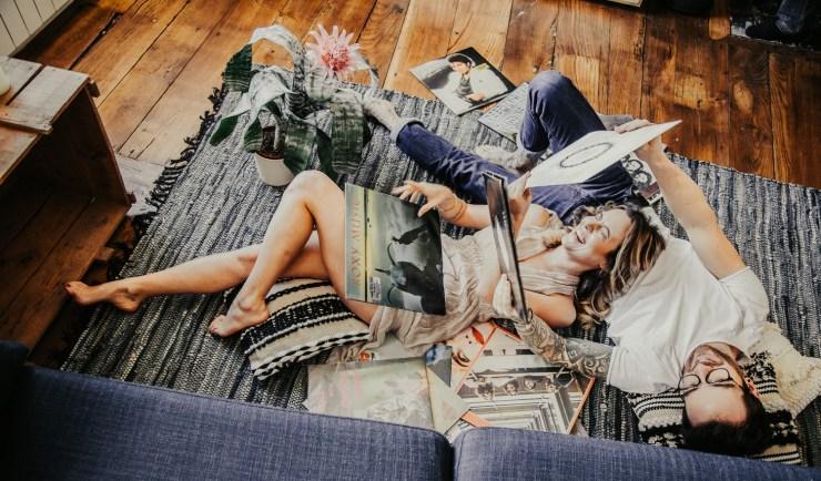 Couple allongé sur le tapis du salon écoutant de la musique