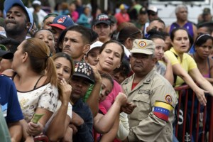 People queue to buy chicken behind a fence at a street market in Caracas on January 24, 2015. With Venezuela's economy in crisis, President Nicolas Maduro announced earlier this week, a 15-percent hike in the minimum wage, and plans to keep a multi-tiered exchange rate system in place.  AFP PHOTO/JUAN BARRETO        (Photo credit should read JUAN BARRETO/AFP/Getty Images)