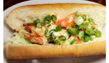 FishBar's Lobster Roll has warm lobster salad with shredded cabbage on a toasted soft roll. It is melt-in-your-mouth delicious!