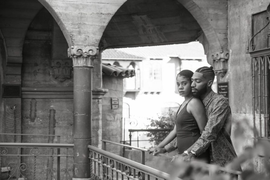Engagement session standing by rail at mission inn
