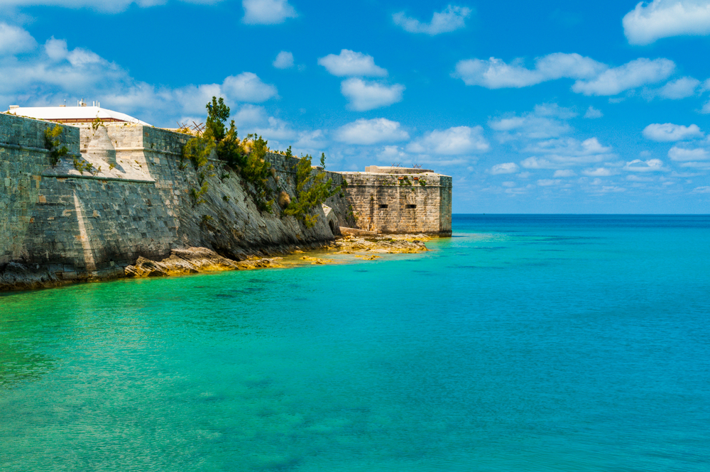 Weathered stone wall against the bright blue ocean in Bermuda