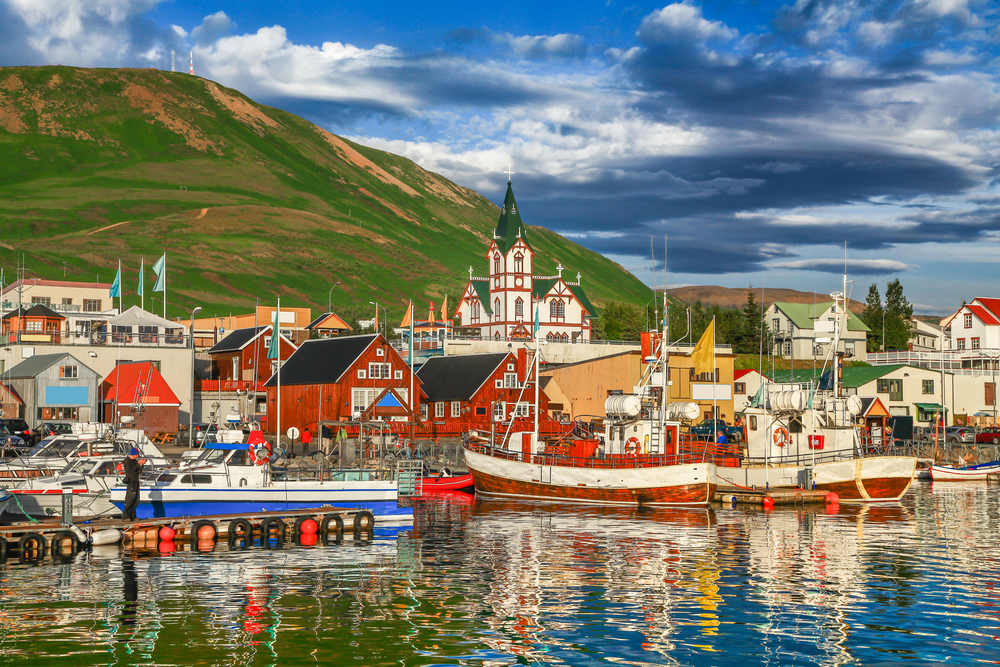 Red and white fishermen houses on the water during sunset in Akureyri, Iceland
