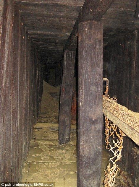 ncredibile condizione: I soldati sono stati sepolti vivi nel fango all'interno del rifugio sotterraneo (foto sopra) che conteneva oggetti tra cui letti, una bottiglia e un elmetto (foto sotto)