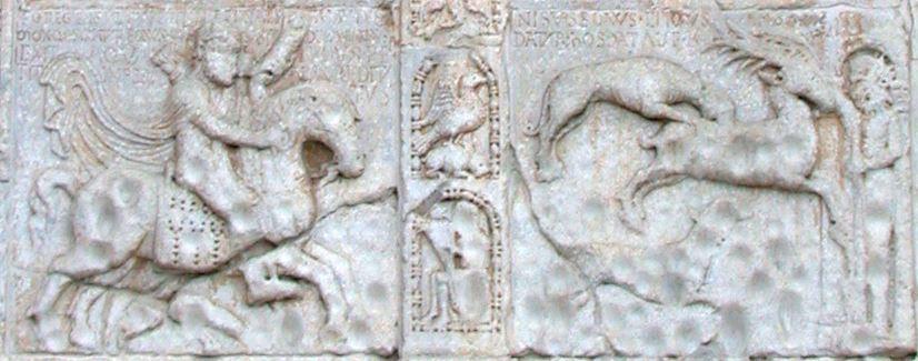 """La Caccia Infernale. Il bassorilievo si trova sulla facciata di San Zeno e raffigura la leggenda della fine di Teodorico che inseguendo un cervo viene precipitato dal suo cavallo demoniaco nel cratere dello Stromboli. La pietra ha un alto contenuto di zolfo e in passato, sfregando una sasso sulla suggestiva scena, le madri di Verona facevano sentire ai loro figli indisciplinati """"l'odere dell'Inferno"""" da cui i fori di cui è ricoperta la scena."""