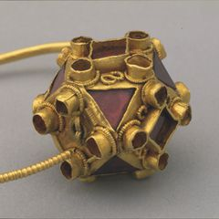 Dettaglio dell'orecchino poliedrico in oro e granati