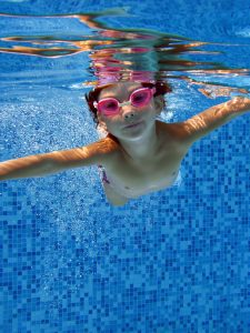Small Child Swimming Underneath Water in Pool