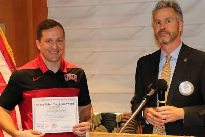 "President Jim presented Coach T.J. Otzelberger with our ""Share What You Can"" award."