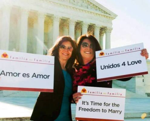 Duran and Pino with signs advocating for marriage equality.